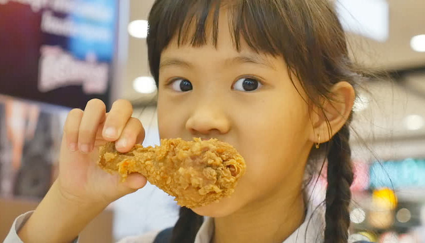 child eating fried chicken